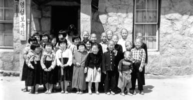 An old, black and white photo, shows a group of Korean children from Compassion's early days of ministry.