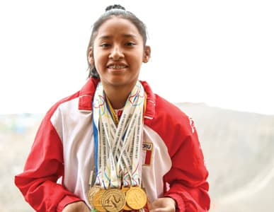 Carmen, the Peruvian national junior champion for rythmic gymnastics, stands, wearing her team uniform, with a large stack of metals hanging around her neck.