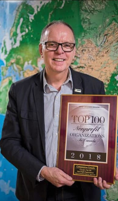 Barry Slauenwhite, the President and CEO of Compassion, stands in front of a large world map, and holds a 'Top 100 Nonprofit Organizations in Canada' plack
