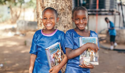 Two girls stand beside a tree holding Bibles and smiling. They wear blue school uniforms