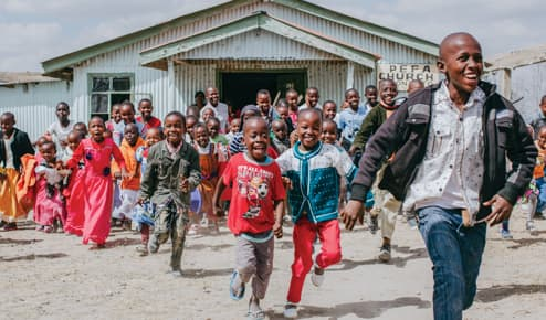 A crowd of children run out of a blue, steel clad church. They are laughing and smiling