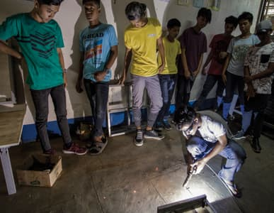 A group fo youth from the Philippines stand around a welder and watch him work in a workshop.