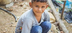 A boy crouches on the ground and smiles up at the camera
