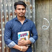 Sujon stands in front of a corrigated metal wall. He holds some books in his arms