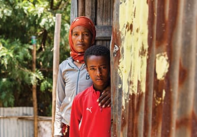 A middle aged boy stands with his mom in the door way of there small home. The home is made out of corrugated steel.