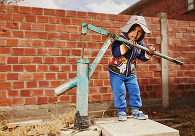 A young girl stands at a hand pumped water well and pushes on the handle.