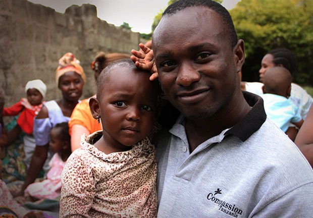 man smiling with child in remote african village