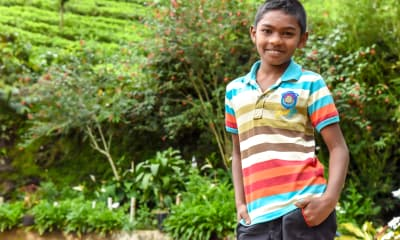 A middle-school aged boy stands in a lush garden. His hands are in his pockets and he smiles