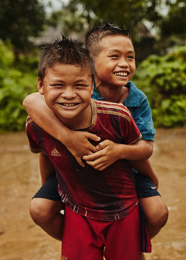 A boy smiles exuberantly as he gives another boy a piggy back ride across a shallow, muddy river.