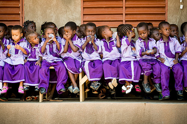 A large group of children sit lined up on benches outside a compassion centre. They are all wearing purple uniforms and having a snack.