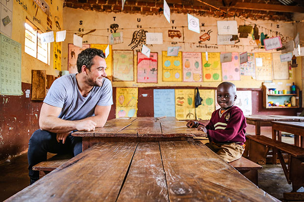 A young man sits across the table from a little boy. They sit in a Compassion centre with colourful art on the walls